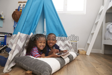 two children lying in tent in