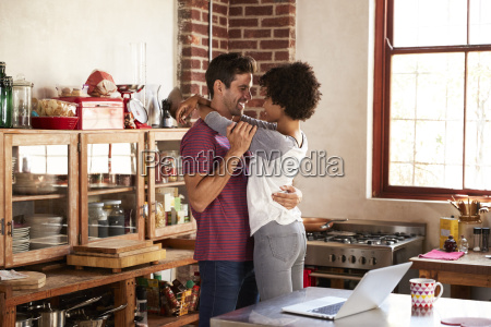 young couple embracing in kitchen three