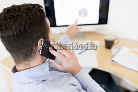 businessman on the phone analysing pie