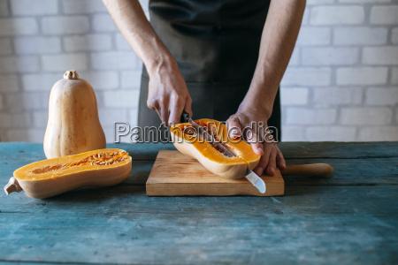 man cutting pumpkin partial view