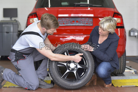 car mechanic with client and tyre