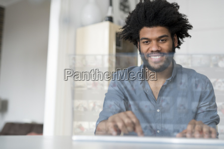 smiling man at home working on