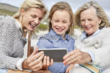 mother daughter and grandmother taking smartphone