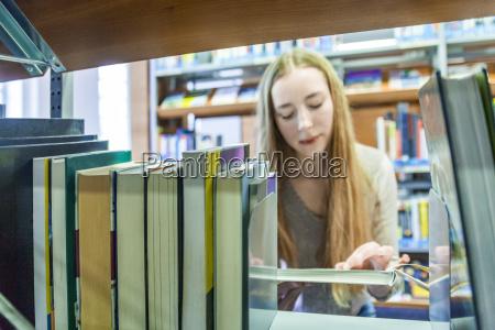 teenage girl behind bookshelf in a