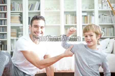 boy flexing muscles for father at