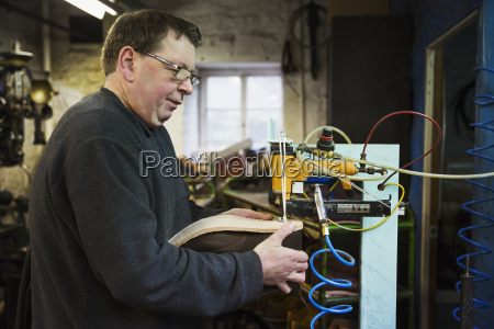 man standing in a shoemakers workshop