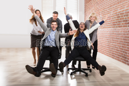 carefree businesspeople making fun in office