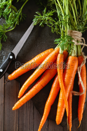 heap of ripe carrots with leaves