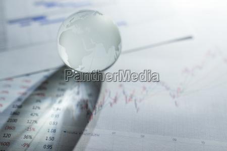 glass of globe over stock market