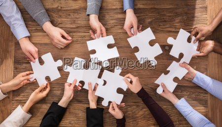 businesspeople hand solving jigsaw puzzle