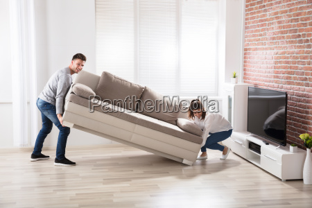 couple placing sofa at their new