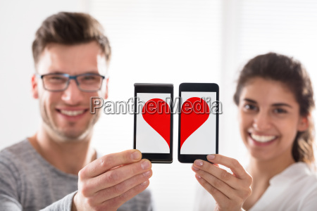 couple showing heart shape on cell