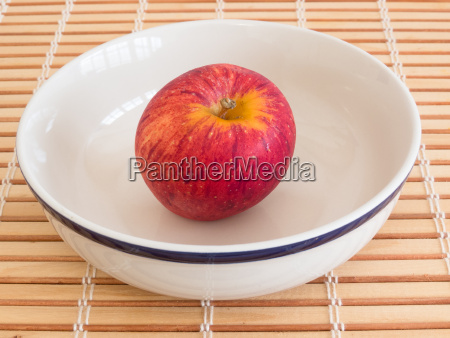 red apple inside bowl on wooden