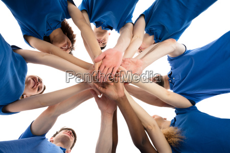 smiling multiracial janitors stacking hands