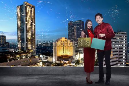 chinese couple wear cheongsam holding shopping