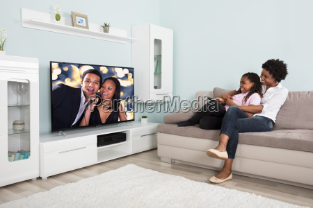 happy mother and daughter watching television