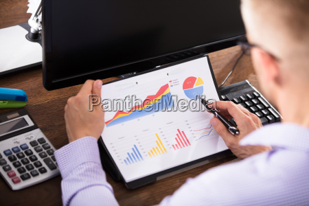 businessperson analyzing graph in office