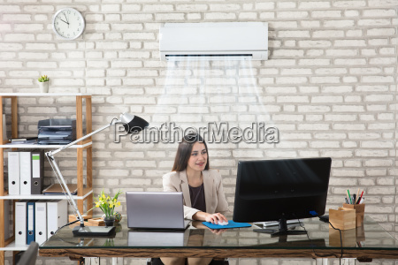businesswoman working in office with air