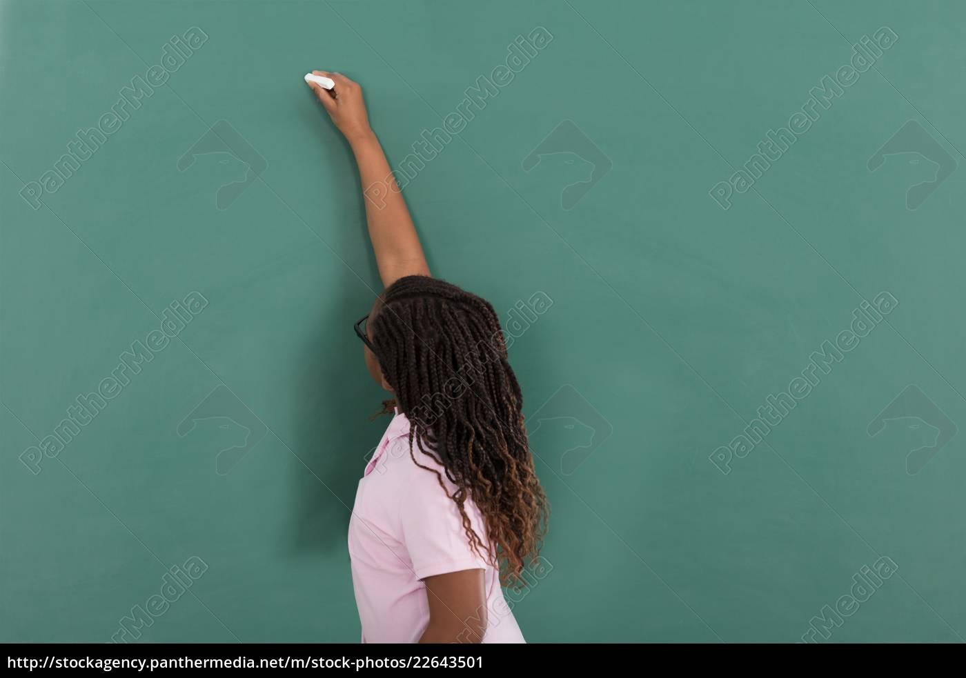girl, writing, on, green, chalkboard - 22643501
