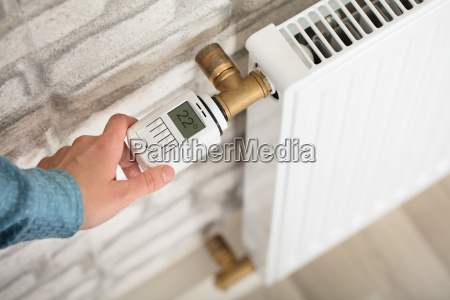 person, adjusting, temperature, on, thermostat - 22643469