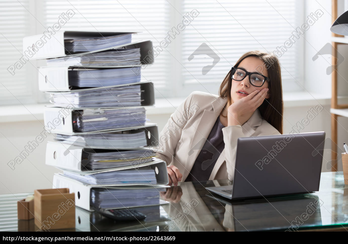 worried, businesswoman, looking, at, folders, stack - 22643669
