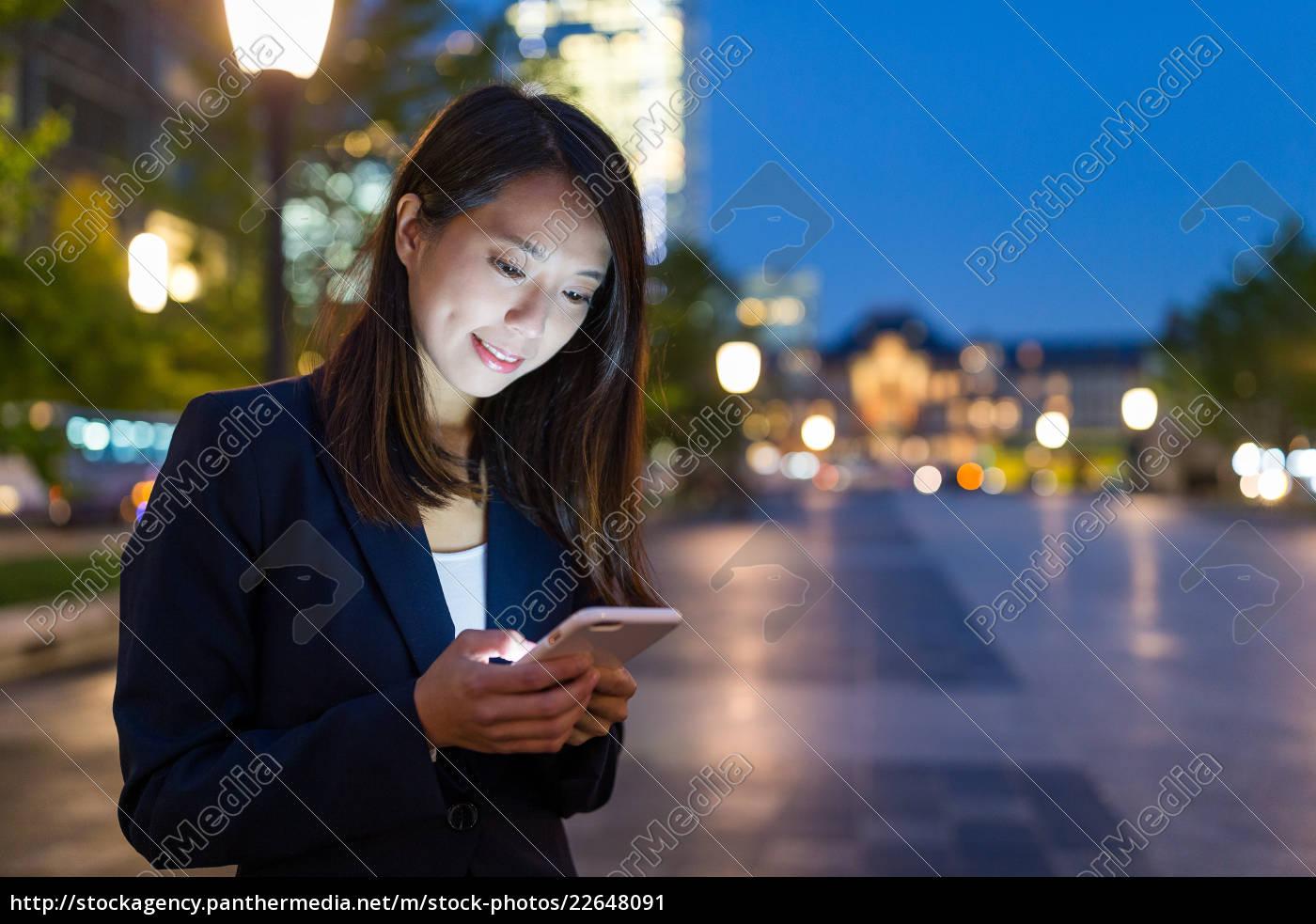 businesswoman, working, on, cellphone, in, tokyo - 22648091