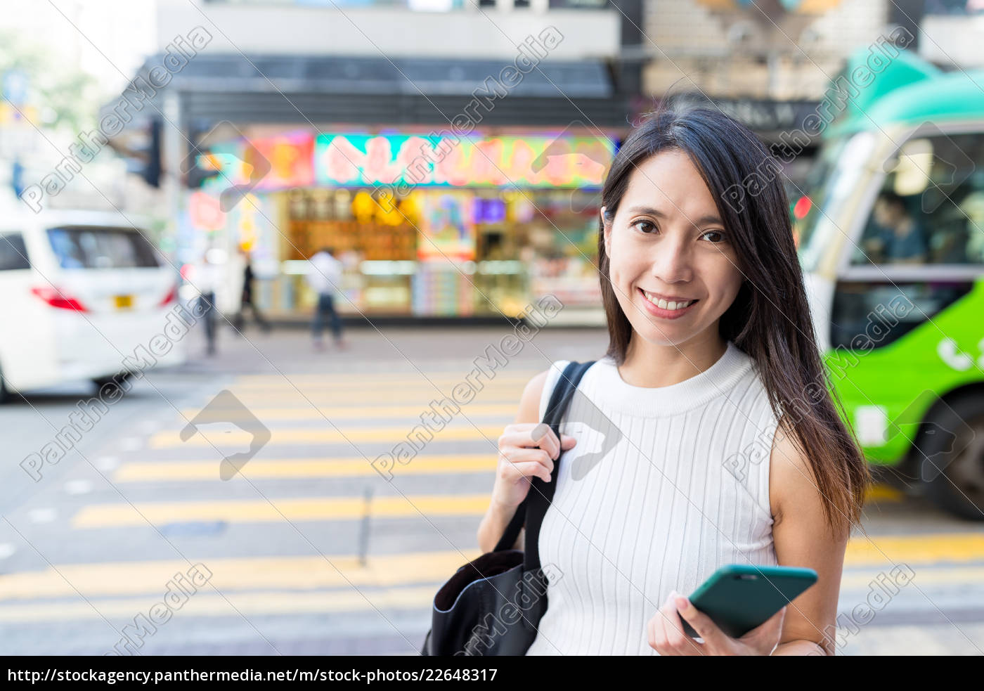 woman, holding, cellphone, in, street, of - 22648317