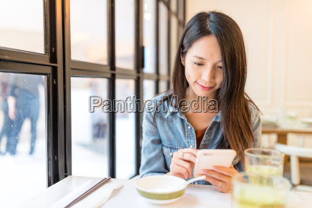 woman, looking, at, cellphone, in, restaurant - 22648099