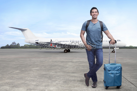 handsome, asian, backpacker, with, suitcase, standing - 22653351