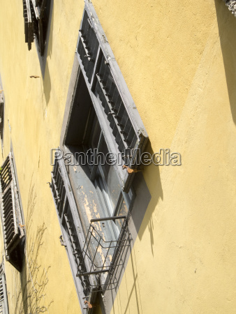 windows with shutters in yellow facade