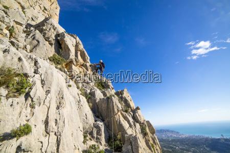 man rock climbing on peak of