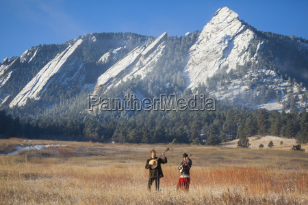 musicians standing in field with mountains