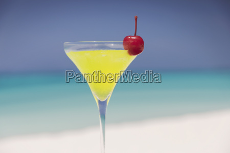 close up yellow cocktail with cherry