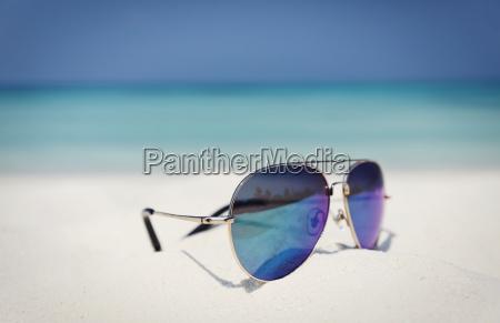 close up aviator sunglasses in sand