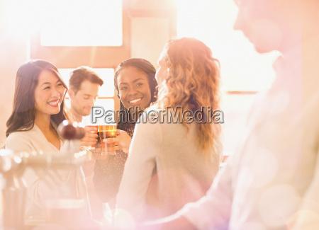 women friends toasting beer glasses in