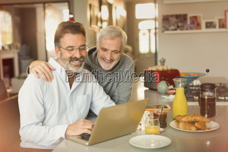 male gay couple using laptop and