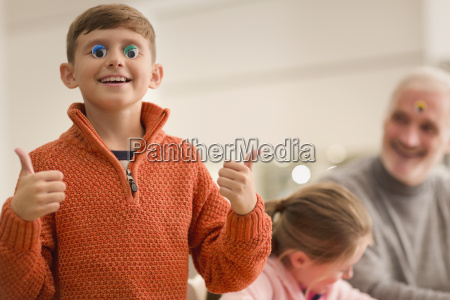 portrait smiling playful boy gesturing thumbs
