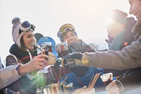 skier friends toasting cocktail glasses apres