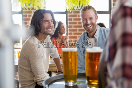 waitress serving two male friends meeting