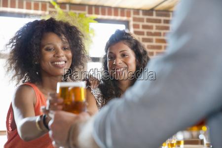 barman serving female customers pints of