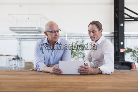 two men sharing tablet in factory