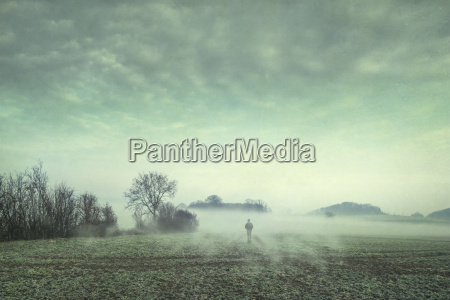 man on field in fog composite
