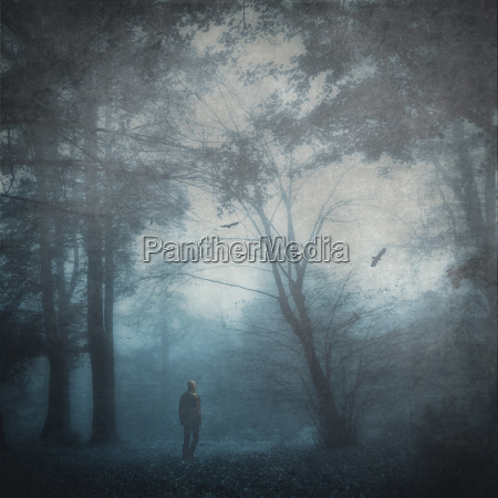 man on forest glade in twilight