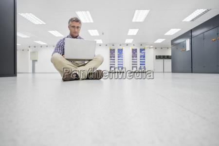 technician sitting on floor laptop working