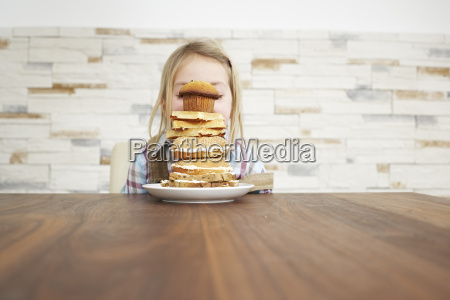 little girl behind stack of baked