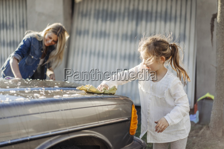 mature woman and girl cleaning car
