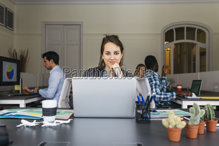 young businesswoman using laptop colleagues working