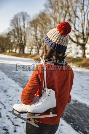 woman on canal carrying ice skates