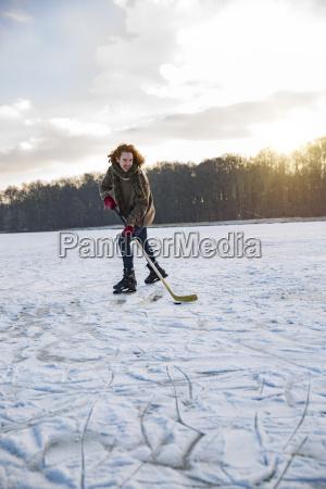 man playing ice hockey on frozen