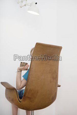 child sitting on armchair holding box